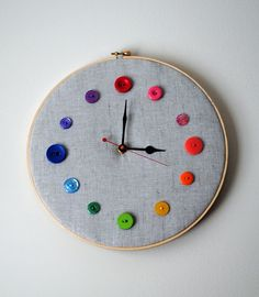An embroidery hoop, a bit of fabric, and some colorful buttons later, and you have the Whimsy Button Wall Clock.