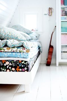 colorful mismatched bedding in white room.  design and photograph by sophia of mokkasin blog