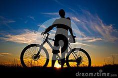 Cyclist with a bike silhouette on a blue sky by Titovstudio, via Dreamstime