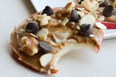 Apple cookies make the perfect snack: Crisp juicy apple slices, smothered with nut butter, then topped with shredded coconut, walnuts and chocolate chips.