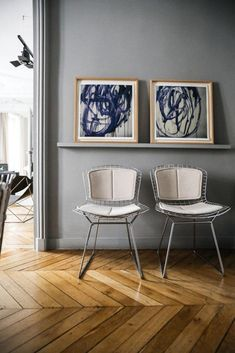 abstract blue art prints in wood frames on picture rail with mid-century modern chairs and herringbone wood floors. #herringbonewoodfloors #woodfloors #midcenturymodernchairs #blueartprints #blueartwork #graywalls #graywallpaint #artprints #framedartwork