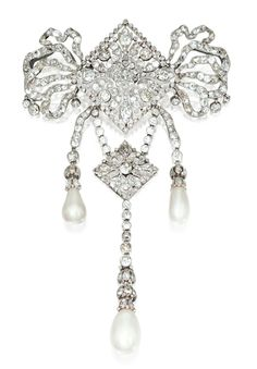 PLATINUM, DIAMOND AND NATURAL CORSAGE ORNAMENT, CIRCA 1910.  The top designed as an openwork stylized bow suspending diamond-set tassels, set throughout with old mine and single-cut diamonds weighing approximately 15.00 carats, three tassels supporting natural pearl drops measuring 12.4 by 12.30 mm., 10.25 by 9.80 mm. and 9.70 by 8.80 mm., with partial signature for Cartier.