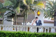 Bride and Groom on balcony of the Waterfront Beach Resort Hilton in Huntington Beach | Jim Kennedy Photographers