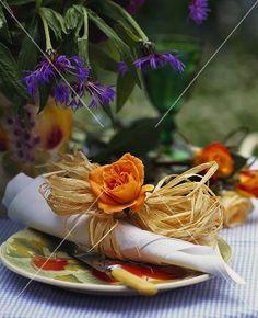 Serviettenring aus Bast und einer Rose, darüber Flockenblumen