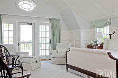 In the owner's paneled bedroom, an antique bow-front chest serves as a nightstand beside the dark-framed bed.