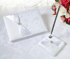 """Michaels.com Wedding Department: Lillian Rose™ White Lace Guest Book and Pen Set It's the little things that will help you remember your big day. This elegant guest book and pen holder set is covered in rich white satin. Each is decorated with white floral lace, a white satin sash and a silver rhinestone flower ornament. The 4x4"""" pen base holds a silver pen with black ink. The 8-1/2x6"""" guest book contains 55 pages for a total of 990 signatures."""