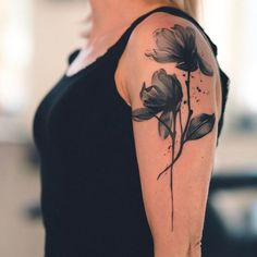 Black watercolor flower tattoo on the left upper arm
