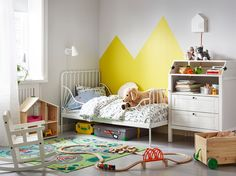 A childrens bedroom with the MINNEN extendable bed against a wall beside the SUNDVIK changing table. A train set is laid out on the floor.