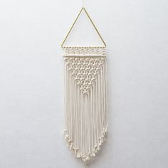 ● D E S C R I P T I O N  Add some minimalistic and modern softness to your room with this gorgeous macrame wall hanging! This hanging is made with 100% cotton cords and brass elements. The perfect combination!   ● D I M E N S I O N S This macrame wall hanging measures:  Width - 27 cm ( 10.5 inches ) Length - 90 cm ( 35.5 inches)   ● S H I P P I N G  This item is ready for immediate shipping!  >> N E W >> Express shipping available to the US for this item! Delivery within 3 working...