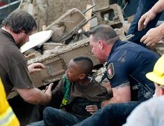 A boy is pulled from beneath a collapsed wall at the Plaza Towers Elementary School following a tornado in Moore, Okla., May 20, 2013. (Sue Ogrocki/AP Photo)