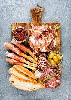 Meat appetizer selection or wine snack set. Variety of smoked meat salami prosciutto bread sticks baguette olives and sun-dried tomatoes on rustic wooden board over grey concrete textured backdrop top view. meat prosciutto diparma salami cured italian selection snack appetizer olive mediterranean sundried tomato meal gourmet delicatessen food wine topview dinner cuisine baguette bread stick grissini concrete textured grey blue table eat platter antipasto set background board rustic wooden…