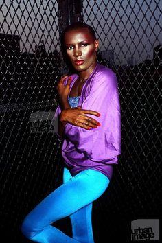 Grace Jones, 1983   urban backdrop chain link fence disco lycra purple & blue