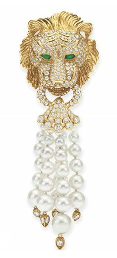 A DIAMOND, EMERALD AND CULTURED PEARL BROOCH, BY VAN CLEEF & ARPELS Designed as a circular-cut diamond and sculpted gold lion's head with pear-shaped emerald eyes, holding a circular-cut diamond hoop in its teeth, suspending a five-strand graduated cultured pearl tassel, measuring from approximately 9.65 to 4.25 mm, with circular-cut diamond terminals, mounted in gold Signed V.C.A. for Van Cleef & Arpels, V