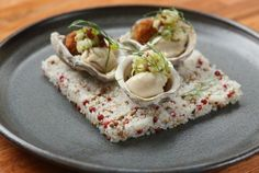 Bâtard's warm Kusshi oysters with fried pig tails and pickles. Photo: Melissa Hom