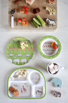 Safari Kids Melamine Dinner Set   Sophie Allport   This Safari themed seven piece dining set includes a plate, bowl, cup, knife, fork, spoon and egg cup. A lovely little gift set for children's birthdays and christenings.  The design features elephants, giraffes, wildebeest, warthogs, zebras and rhinos on a green background. Bound to appeal to fans of African animals.