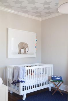 White and gray boy's nursery features a ceiling clad in gray stars wallpaper, Serena & Lily Stars Wallpaper, placed over a wall lined with an The Animal Print Shop Baby Elephant Print placed over an Oeuf Sparrow Crib draped with a blue pom pom throw blanket and a round accent table placed atop a blue rug.