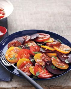 Slices of roasted beets and fresh beefsteak tomatoes are dressed with shallot vinaigrette and fresh oregano to create a colorful and flavorful salad.