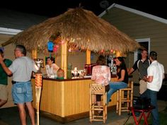 HGTV takes outdoor entertaining to new heights by building a three-sided tiki bar with bamboo accents and a grass roof.