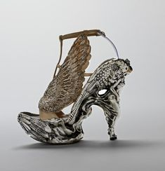 McQueen Savage Beauty F/W 2010 heel in the shape of an angel is accompanied by feathers in relief along the sole of the shoe. A pair of silver embroidered wings frame the foot, suggesting imminent flight. This sense of motion is strengthened by the angel's resemblance to a figurehead poised at a ship's prow.suggests a reference to 17th c master woodcarver Gibbons.known for his highly detailed work that involved both carvings in relief and intricate openwork carving, as in a limewood cravat.