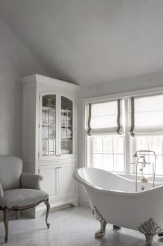 White and grey French bathroom features gray sloped ceilings and walls lined framing windows ...