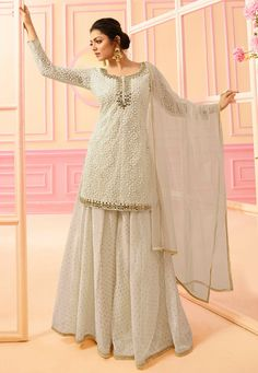 Bollywood diva drashti dhami style off white designer palazzo suit online which is crafted from net fabric with exclusive embroidery and hand work. This stunning designer palazzo suit comes with chanderi jacquard bottom santoon inner and net dupatta. Lehenga Choli, Robe Anarkali, Pakistani Sharara, Sharara Suit, Pakistani Dresses, Indian Dresses, Indian Outfits, Patiala, Salwar Kameez