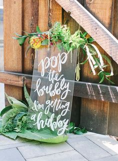 """Rustic bridal shower idea - clear sign """"pop the bubbly, I'm getting a hubby"""" sign with greenery {Courtesy of Inspired By This}"""