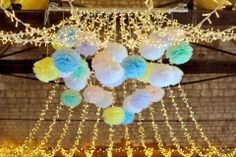 White, mint, sky blue, lavender, lemon and baby pink pom poms in the middle of a fairy light wedding canopy