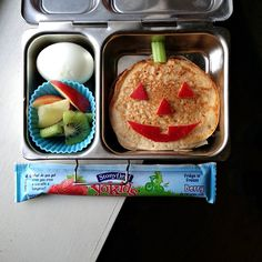 pancake jack o lantern lunch: apple skins and celery stalk, hard boiled egg, apple slices and kiwi, yogurt tube