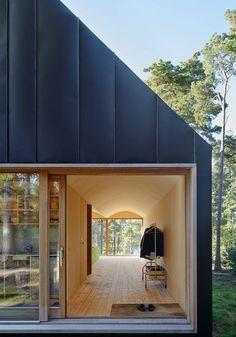 Det er plassert tre store skyvedørsseksjoner i hytta, to av dem på hver fasade og den siste på den ene langveggen. Det gir et stort lysinnslipp til interiøret og forsterker den lette karakteren som bruken av finérplater skaper. / Tham & Vingård