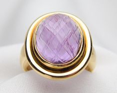 Yves St. Laurent Amethyst Ring. This stunning midcentury cocktail ring features a 9.25 carat, faceted cabochon-cut Amethyst in a 18KT Gold bezel setting. The ring is signed: Yves. •$2,700.00