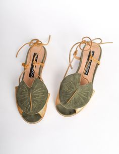 "Amazing vintage Maud Frizon sandals featuring a large lily pad applique detail across the top. Gold metallic leather mixed with sage green suede and metallic threaded detailing. Corded sides that pass through and tie at the back of the ankle. Suede & leather lined sole. Very cool and funky, true to Maud Frizon's creative personality and designs. Maud Frizon Made in Italy Leather / Suede Size 36.5 EU ( 6.5 US) Measurements: Insole 9"", Width 3.25"", Heel 3/8"" Condition: This pair of shoes is..."