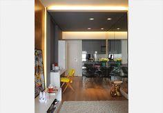 """Na integração de espaços que ampliou o living deste apartamento, as vigas e os pilares exibem o aspecto bruto do concreto, que também ficou aparente no teto. O rebaixo de gesso acartonado em """"U"""" tem a largura da área de circulação e embute a iluminação de lâmpadas fluorescentes. Projeto do estúdio Superlimão"""