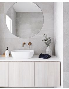 Clean lines and large format grey tile covers the floor and walls. A round frameless mirror hangs over a white sink with brass wall mounted bathroom sink faucet. The flat paneled vanity is wall mounted and has a thin white countertop Bathroom DOT + POP Laundry In Bathroom, Interior, Wall Mounted Bathroom Sinks, Round Mirror Bathroom, Bathroom Interior, Wall Mount Faucet Bathroom Sink, Bathrooms Remodel, Bathroom Decor, Tile Bathroom