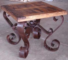 The Old Wood Mesa Porfirio features a top made from old and reclaimed wood, paired with a forged wrought iron base.