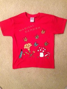 Magic Garden Children's Size Small (Gildan brand shirt). Turn out the light, and watch the magic begin. Flowers and butterflies glow in the dark, and even crickets dress to the nines, in their top hats, attend Garden Parties, where you, the special little friend, are invited. All of our shirts and bags are hand drawn, (NO stencils used) and then hand painted. At www.bonanza.com/booths/DevKelTees