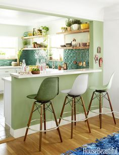 """In Justina Blakeney's """"Jungalow,"""" the wall between the kitchen and dining area is fittinglypainted in Breakfast Room Green by Farrow & Ball. Moroccan clay tiles from Badia Design cover the kitchen backsplash, and the Silestone countertop is from Lowe's."""