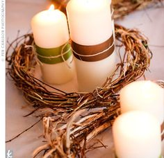 Center pieces. White candles with green and brown ribbon and raffia surrounded with flowers