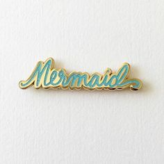 "Let everyone know you're really a mermaid! Also available in Pink Glitter. Details - 0.5"" x 2"" size - Cloisonné hard enamel set in 22kt plated gold - Rubber clutch clasps - Illustrated & © by Brianna"