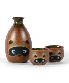 """Raccoon sake bottle and cups - cute! #product_designTanuki, modern, ceramic. Sake Kai Tanuki 酒買狸 (lit. Tanuki Procuring Sake). Depicted with big tummy, staff, giant scrotum, straw hat, sake flask, and promissory note. Welcoming icon found frequently outside Japan's bars and eateries (""""come in, don't be stingy""""). Also a wealth-bringing icon adorning gardens. Photo from Rakuten J-store"""