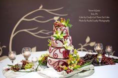 My amazing Winery-Hawaiian themed wedding cake: brown marbled fondant, burgundy swirls, green orchids, red and green grapes, and sand-filled wine glass candle holders.  The cake was a triple-layer pistachio, chocolate, & red velvet all in one slice to match the color scheme!