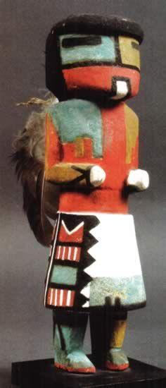 Tuma-öi (White Chin Kachina), circa 1930, 21 cm Ce Kachina de tradition très ancienne chez les indiens Hopi intervient lors des cérémonies du Powamu (fête du Haricot). Il n'a pas été utilisé lors des danses ces dernières années. Sa fonction primaire était d'apporter la pluie.
