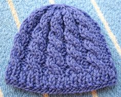 This pattern is a tiny cabled preemie hat knit from the bottom up with a ribbed brim. I designed this pattern in the Fall of 2009 as part of a personal project to knit a dozen preemie hats for charity!