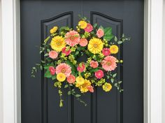 This fun and colorful spring wreath is an original twoinspireyou design. Lifelike yellow, pink, and salmon-colored Gerber daisies, along with