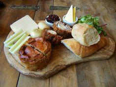 Ploughman's Board of pork pie, scotch egg, mature cheddar, artisan bread, pickled onions, branston pickle, and celery. Credit Matt, flickr