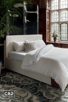 Starting her career in the NYC fashion industry, designer Sasha Adler's fully upholstered bed clearly draws from her editorial background. Covered all the way around in a textural ivory linen, bed is trimmed with genuine leather piping and leather-wrapped corners. Mattress will sink into the frame slightly, making it easy to tuck bedding in and keep things tidy. CB2 exclusive.