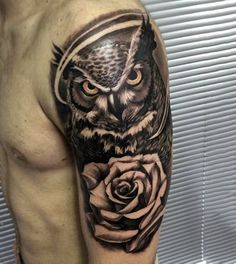 Realism style cool looking shoulder tattoo of big owl with rose flower