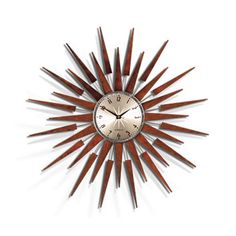 """Hanging in your study or anywhere in your house, the Bursting Spokes of Time clock has a silvery metal center that conceals a high-quality quartz movement. Its bursting """"rays"""" are made from gorgeous dark wood, framing its metal face with beautiful symmetry."""
