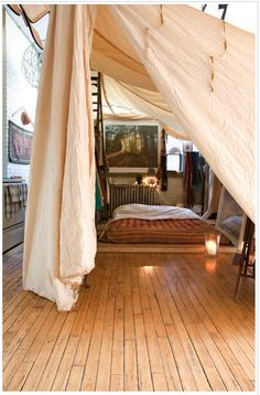 I love this grown up fort, employing an old parachute, and futon on the floor, a candle and a mirror.