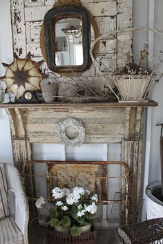 This faux fireplace is very effective because it effectively uses layering to add to the fool the eye arrangement.  On first glance, the iron headboard appears to be a fire screen. Attention then moves to the arrangement on the mantle and the mirrors above it.  The flower arrangement further distracts from the faux.