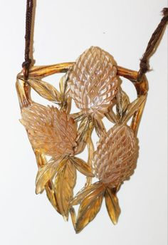 An Art Nouveau stained horn pendant, by Elizabeth Bonté  Modelled to depict a trio of pineapples, heightened in shades of green and brown, within a shaped triangular frame, signed to the reverse, suspended from a brown cord with horn and pink paste spacers, pendant length 7cm, cord length 83cm.